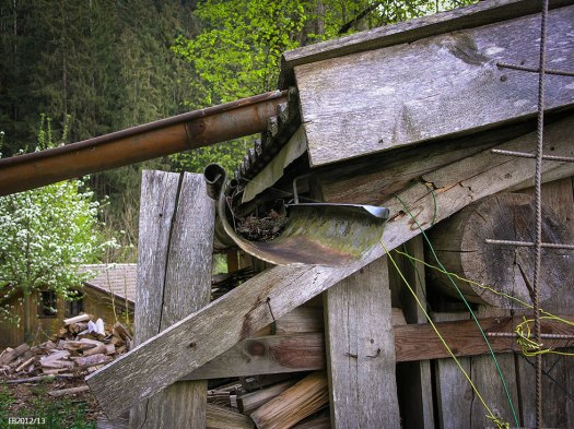 Photo. Part of a wooden shed in a mountainous area.
