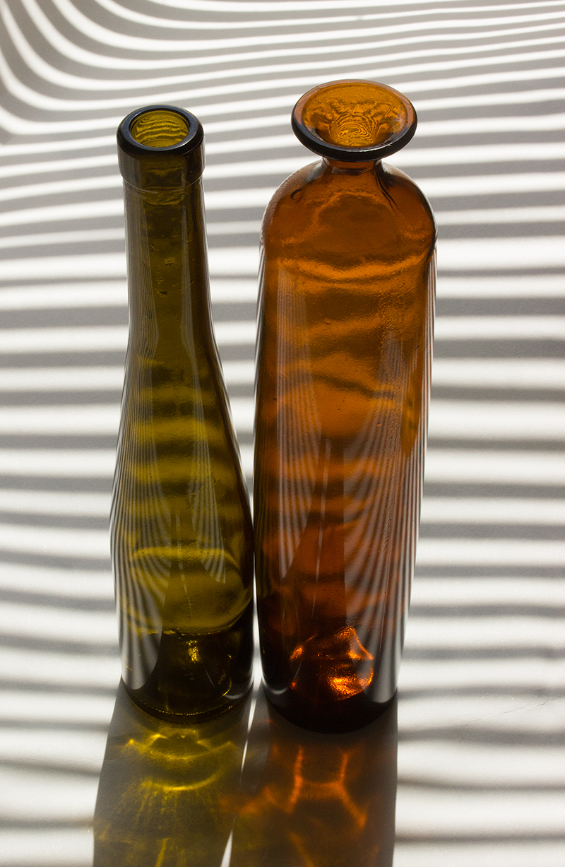 Colored bottles, cleaned, and drying in the morning sun.