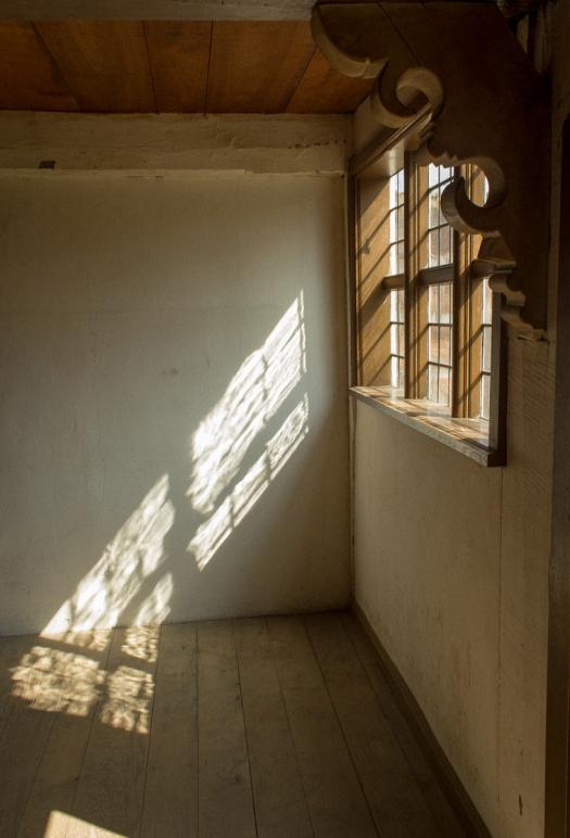 Oblique light streams through the checkered window
