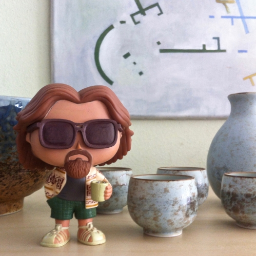"""Photo of a figurine of Jeffrey """"The Dude"""" Lebowski, a character in """"The Big Lebowski"""" on a bookcase with a sake set and painting by Eelco Bruinsma."""